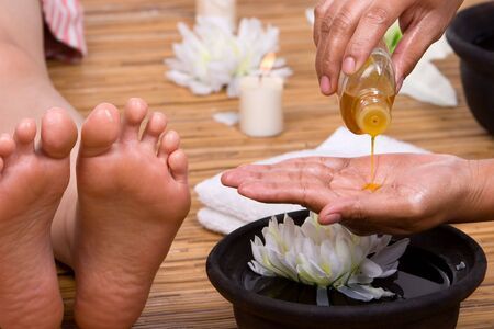 The beautician is pouring the aromatic massage oil into her hand.