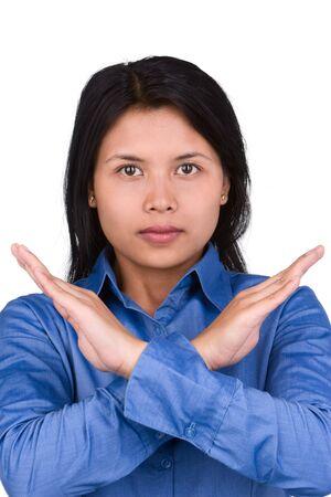 objecion: Una joven mujer de gesto para expresar su protesta por crosing su mano delante de ella. Dispara contra la muy brillante de color blanco como fondo de pantalla para separarse naturalmente el modelo. Foto de archivo