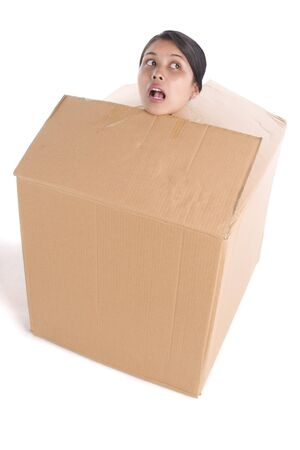 trapped: A head of young woman is stuck inside the box, shot on white background. Stock Photo
