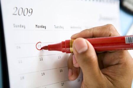 monday: Circling the date 5 on January 2009 calendar (Monday).