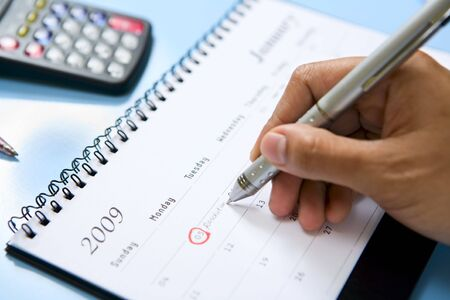 A hand is writing on the calendar. Focus is on the tip of the pen.