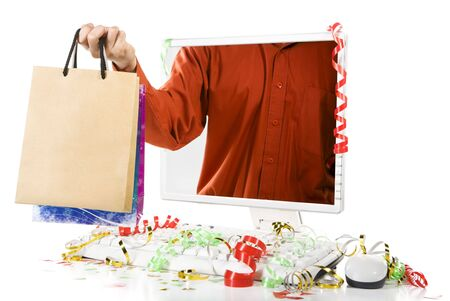 A man is holding paper bags from inside computer's screen. Confetti scattered around the computer. Stock Photo - 3914976