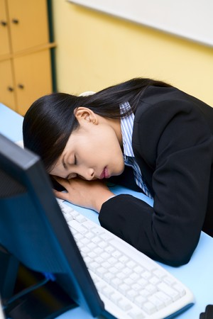 A young woman is sleeping in front of her computer. photo
