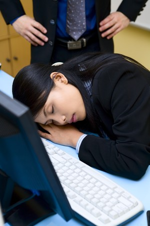 A woman employee is caught up sleeping in office by her boss. photo