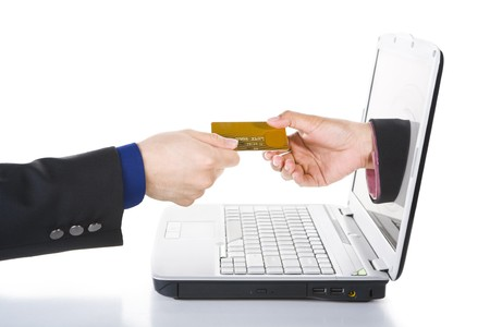 A hand comes out from laptops screen is receiving payment using credit card.