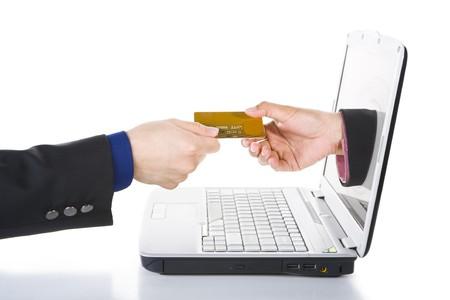 transaction: Een handje afkomstig van scherm van de laptop is ontvangen betaling maken per creditcard. Stockfoto