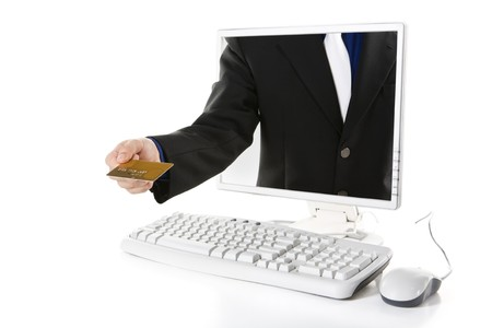 A hand is holding gold credit card from inside computers screen. All important data on creadit card has been removed andor removed. photo