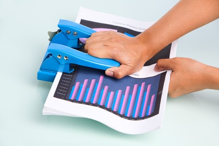 leverage: Employees hand is pressing hole puncher where the documents placed in. Taken from side view.