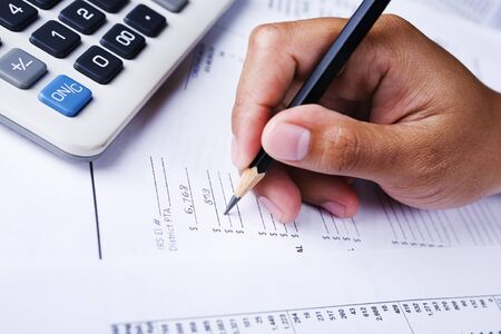 ledger: A hand holding a pencil is writing on financial report form Stock Photo