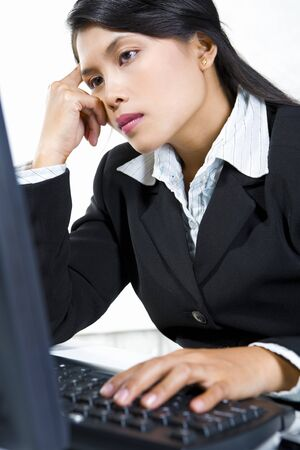 Portrait of a young businesswoman look ver sluggish in front of her computer in office. photo