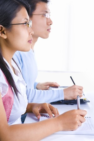 Side view of young man and woman writing on their notebooks in class. photo