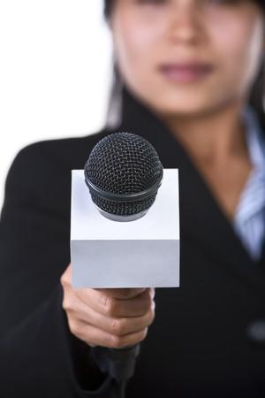 reportero: Una mujer es la celebraci�n de un micr�fono a la c�mara. Disparo contra el fondo blanco. Foto de archivo