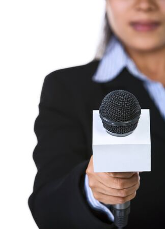 directly: A female host is holding a microphone pointed directly to the camera. Shot against white background.