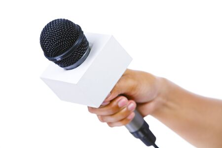 Side view of a bare hand holding a microphone aiming to the empty space on left. Shallow depth of field, focus mainly on microphones tip.