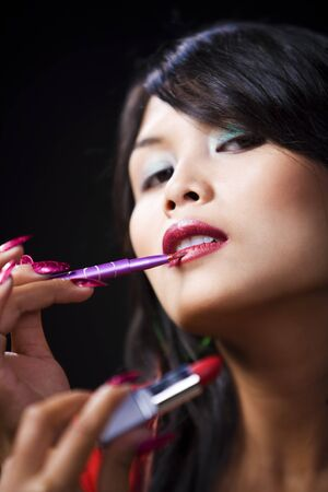 A young woman is applying lipstick on her lips using brush while looking at the camera. Shallow depth of field, contrast against dark room behind. photo