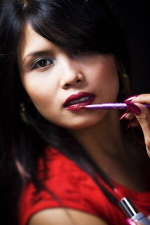 A young woman using a lipstick brush. Very shallow depth of field, high contrast. photo