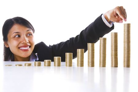 the end of the year: A young Asian businesswoman happily pointing at the highest stack of coins represent the end year profit of her investment. Main focus on coin stacks. Stock Photo