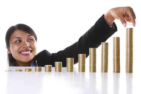 highest: A young Asian businesswoman adding one coins to the highest stack in the most right row. Twelve stack of coins represent twelve months in a year.