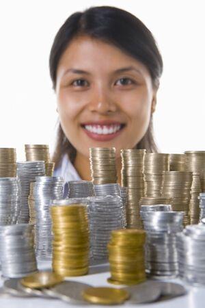 south east asian: Una joven mujer en el fondo sonriendo a la c�mara, delante de su gran cantidad de pilas de monedas. Asia Sudoriental monedas utilizadas aqu�.