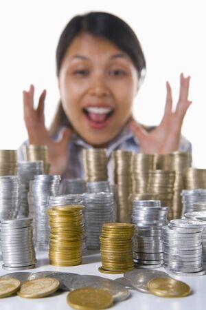 south east asian: Una mujer grita en el fondo feliz de ver los beneficios de su inversi�n. Asia Sudoriental monedas utilizadas aqu�.