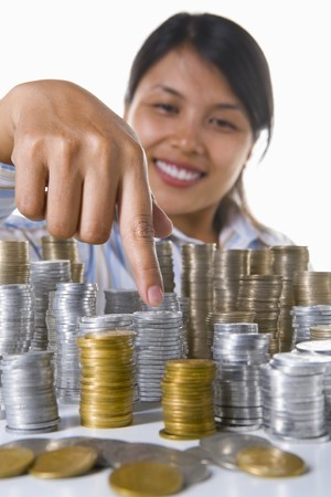 south east asian: Una mujer en el fondo apunta a la pila de monedas de oro. Asia Sudoriental monedas utilizadas aqu�.