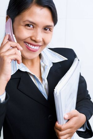 pone: Portait of a young Asian businesswoman listening to her cell pone and smiling to the camera. Stock Photo