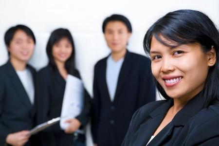 south east asian: J�venes de Asia del Sudeste Businesswoman sonriendo a la c�mara con otras personas de pie y frente a la c�mara de fondo.