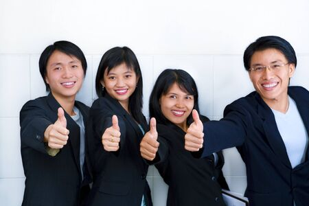 chinese businessman: All foung young Asian showing their satisfaction with thumbs up. (Note: main focus on the thumbs, faces are blurred) Stock Photo