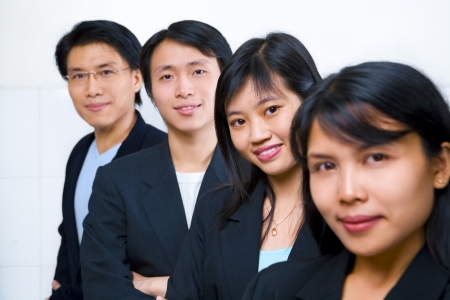 asian man face: Young Asian business people line up, with focus on the second front woman (Chinese woman) Stock Photo