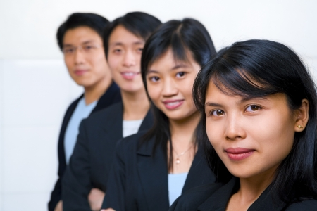 south east asian: Young Asian business people line up, with focus on the front woman (South East Asian woman)