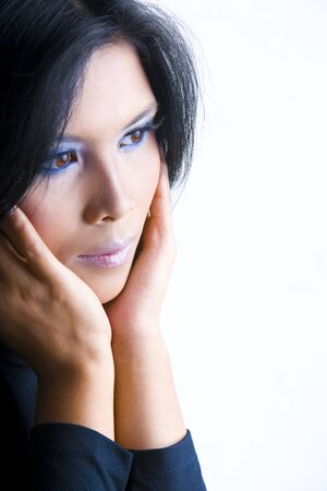A young beautiful Asian woman feeling lonely, shot aginst white background. Focus mainly on the left eye, doing a bit smoothing to the darker area of nose and cheek. photo