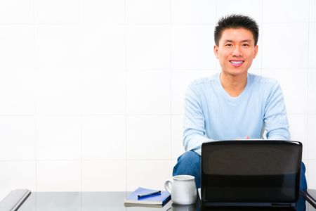 scholar: A young happy scholar sitting in front of his laptop at home. Stock Photo