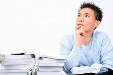 scholar: A young scholar is looking away - thinking for an idea. Stock Photo
