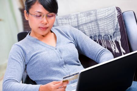 Young Asian woman using her gold credit card for online transaction photo