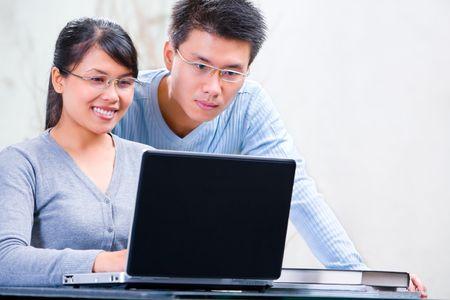 hombre estudiando: Pareja joven de Asia navegaci�n de Internet en casa