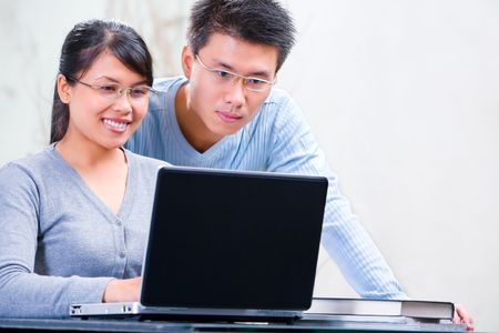 Young Asian couple browsing internet at home
