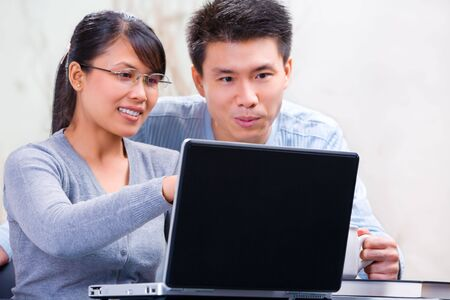 tutor: Young Asian woman showing something on the laptop to her partner