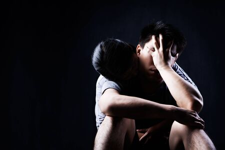 A man is sad and being consoledembraced by his partner photo