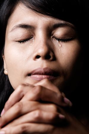 Asian woman is praying and shed tear.