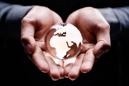 Hands holding a glass globe showing Africa, Europe and part of Middle East photo