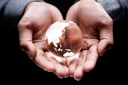 Hands holding a glass globe showing Asia and Australia continent photo