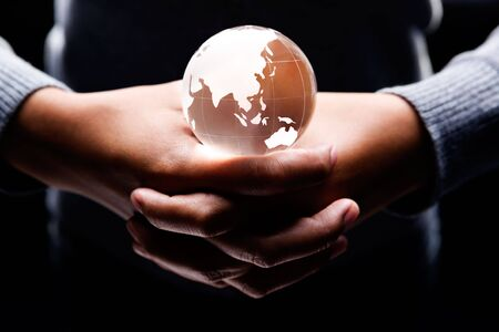 both hands holding a glass globe on it showing Asia and Australia continent