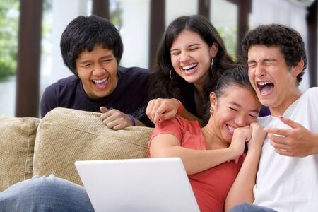 people laughing: A group of multi ethnic student laughing at something on the laptop.