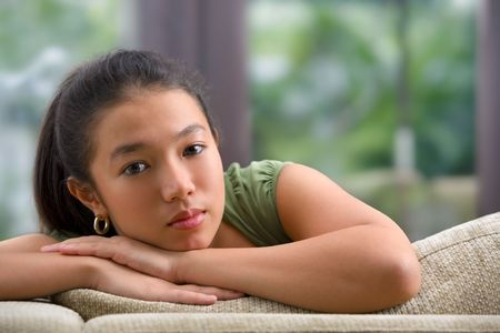 tenager: A Female tenager sitting on sofa at home pose to camera