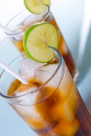 soft drinks: High angle shot of two glass soft drinks, with sliced lime and straw on blue surface