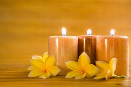 Arrangement of aromatic candles with frangipani on bamboo mat as background photo