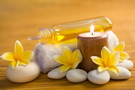 Aromatic candle, soap bar and essence oil with frangipani flower and white stone around it photo