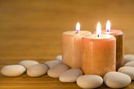 bamboo mat: Three aromatic candles and stones with bamboo mat as background