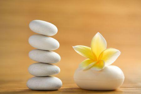 Zen stone, aromatic soap bar with frangipani flower on bamboo mat photo
