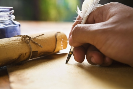 feather pen: Hand writing on old parchment  paper using quill pen